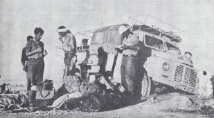 YNK229F sank through the crust in the salt desert in Iran - the Dasht-e Lut . After 24 hours digging the truck still could not be extracted. Eventually, a tractor was found to pull it out. Standing on the left is Stuart Jenkins eating beans from a can, Larry Weiss is standing next to Stuart and on the far right is Larry, a freelance photographer from the USA. Clive Imrie is seated in the back of the truck.