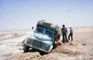 YNK229F sank through the crust in the salt desert in Iran - the Dasht-e Lut . After 24 hours digging the truck still could not be extracted. Eventually, a tractor was found to pull it out. Larry Weiss is standing next to the truck; Martin Hayes is on the right.